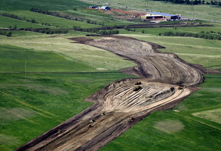 Heavy machinery plows through farmland for the construction of the U.S. Route 85 bypass around Watford City, N.D., June 12, 2014.