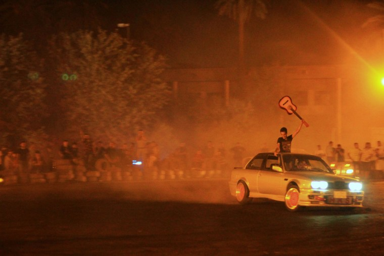 """Young Iraqi men gather to watch souped up cars intentionally spin out and skid: a dangerous sport called """"drifting."""""""