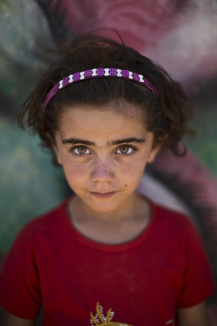 Image: Syrian refugee Samah, 5, poses at Zaatari refugee camp, near the Syrian border, in Mafraq, Jordan on July 29