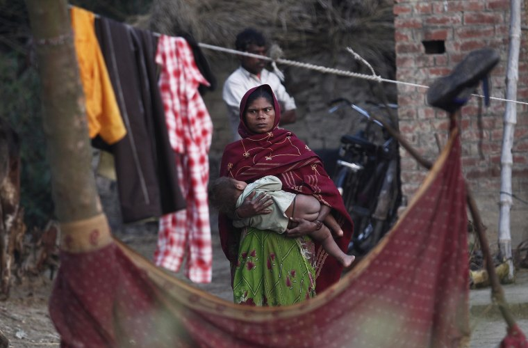Image: A woman holds her child as she stands outside her house at Dalit village of Bhaddi Kheda in the northern Indian state of Uttar Pradesh on Jan. 15, 2012.