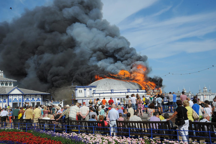 Image: People look on as file engulfs the Eastbourne pier in Eastbourne, Britain