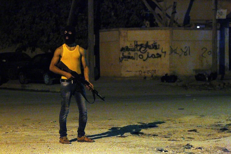 Image: A masked Libyan gunman stands on a street in the eastern city of Benghazi