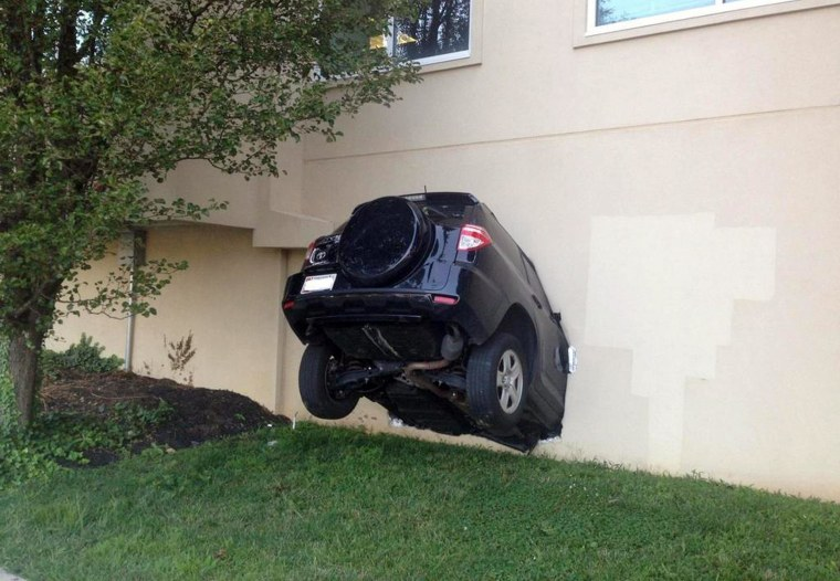 Image: An SUV hangs out of the side of a building that houses county offices after its driver drove into the building, injuring three people