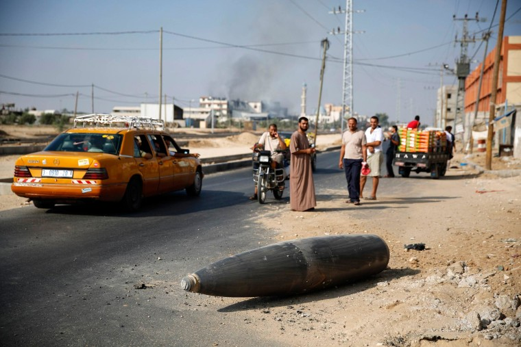 Image: Palestinians look at an unexploded Israeli shell that landed on the main road outside the town of Deir Al-Balah in the central Gaza Strip