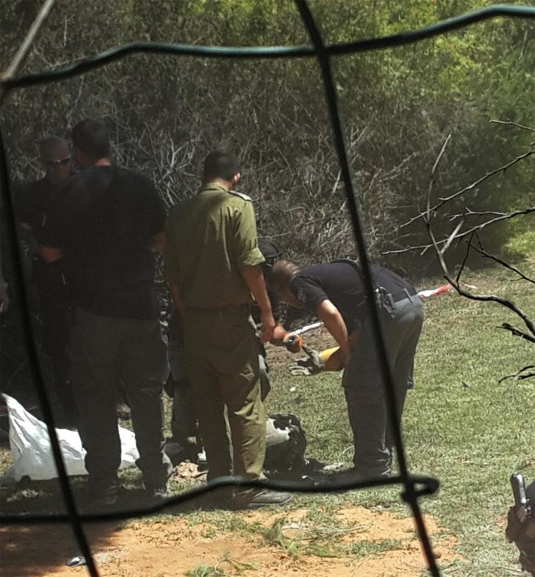 Israeli military personnel inspect the remains of a Hamas rocket that landed in the yard of a home in the Savion neighborhood of Tel Aviv, Friday, July 25, 2014.