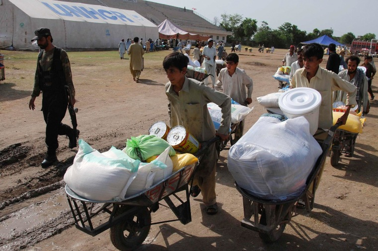 Image: Boys fleeing military offensive in North Waziristan receive relief handouts in Bannu