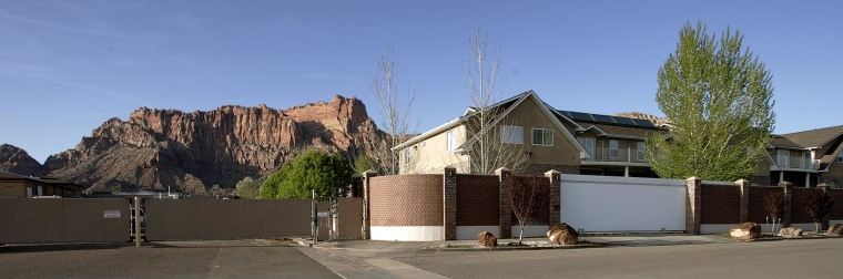 """Image: Tall walls, fences and \""""no access\"""" signs surrounds the homes of Warren Jeffs on April 20, 2006 in Hildale, Utah."""