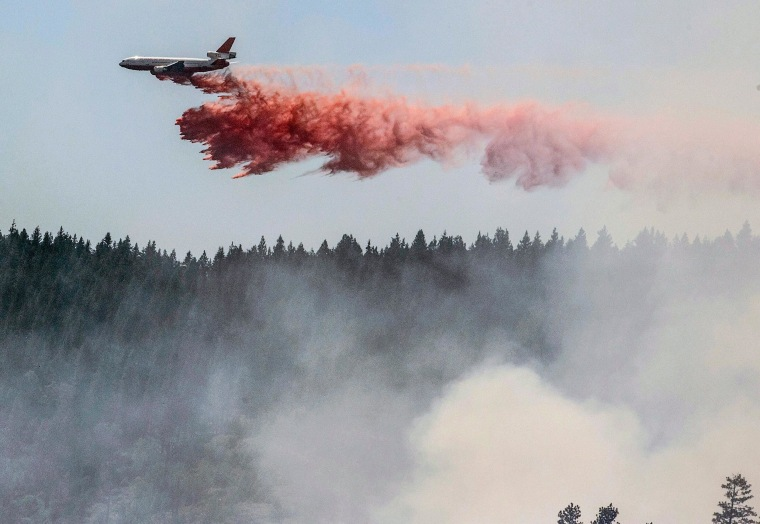Image: A plane drops fire retardant as firefighters battle a blaze in El Portal, Calif., near Yosemite National Park