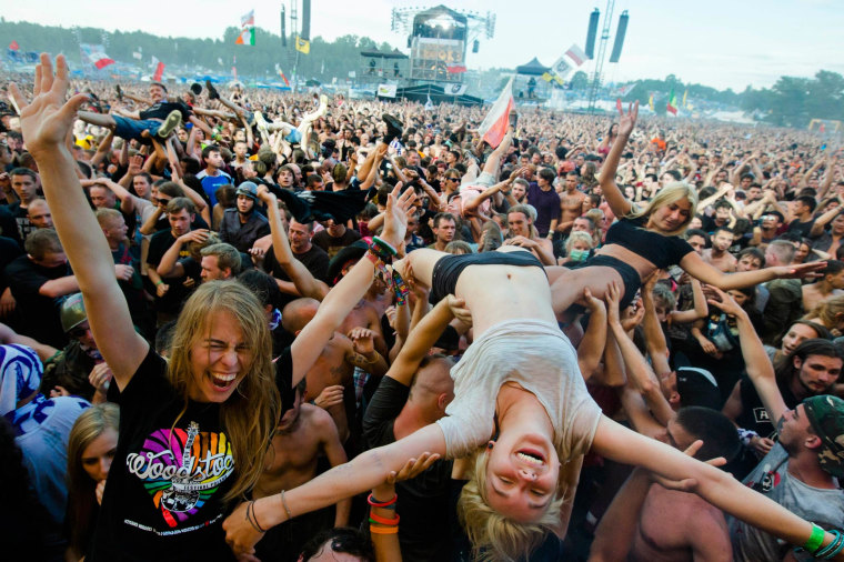 Image: A woman crowd-surfs in front of main stage at the Woodstock Festival in Kostrzyn-upon-Odra, close to the Polish-German border