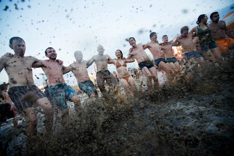 Image: People dance in a mud pit near the main stage at the Woodstock Festival in Kostrzyn-upon-Odra, close to the Polish-German border