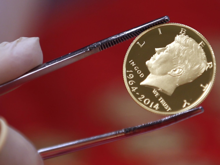 Image: A newly-stamped gold coin of President John F. Kennedy is examined at the U.S. Mint at West Point