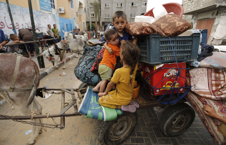 Image: Displaced Palestinians leave a United Nations school in Beit Lahia