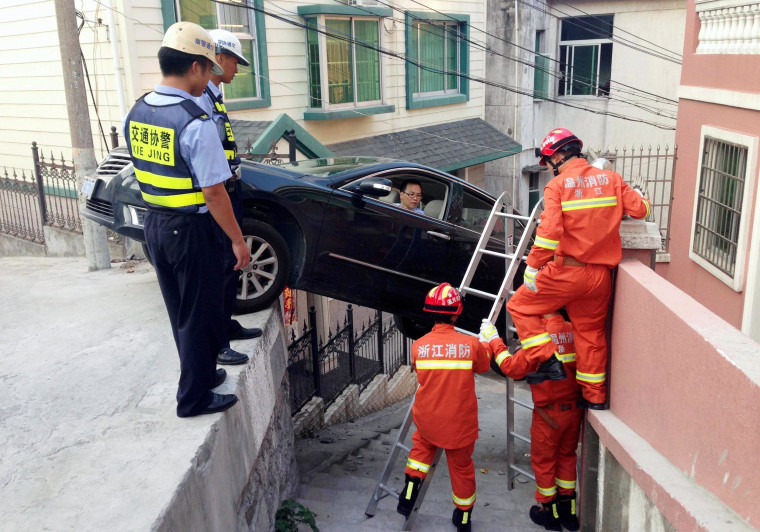 Image: Rescue workers try to help a driver out of his car, after the vehicle was stuck over an alley in Wenzhou, Zhejiang province