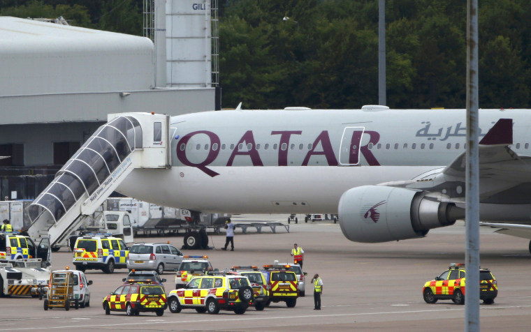 A Qatar Airways aircraft is seen surrounded by emergency vehicles at Manchester airport in Manchester, northern England Aug. 5. A British fighter jet escorted a passenger plane into Manchester airport on Tuesday after the pilot reported that a suspect device was possibly on board, police said.