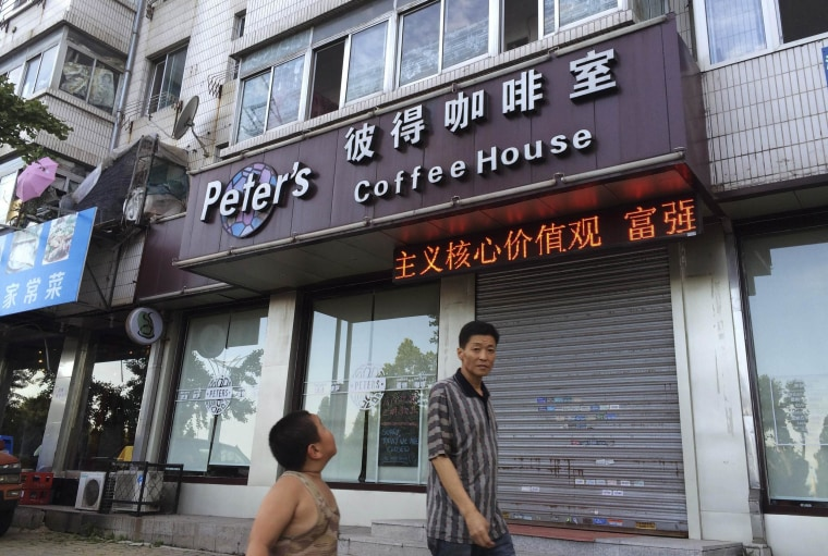 Image: A boy looks up as he walks past the closed coffee shop owned by Canadian couple Kevin Garratt and Julia Dawn Garratt in Dandong, Liaoning province