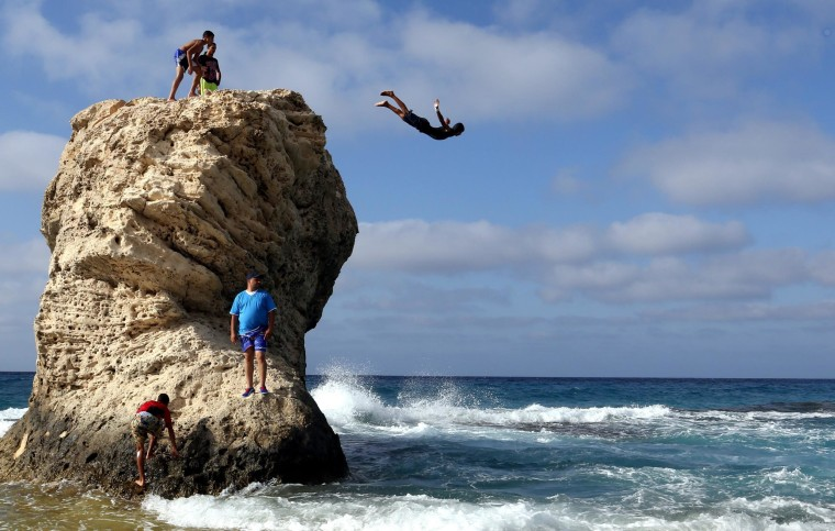 Image: An Egyptian boy dives off Lila Murad rock in Marca Matroh, Cairo