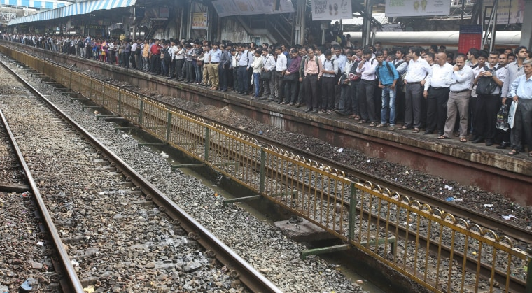 Image: Indian commuters wait on an over-crowded platform to board a local train at a suburb railway station in Mumbai.