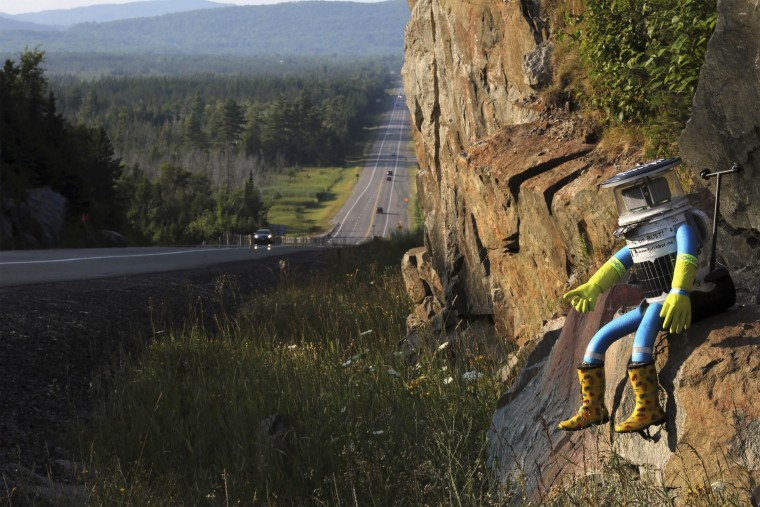 HitchBOT is seen posed next to Highway 17 north of Sault Ste. Marie, Ontario, and a portion of the Trans-Canada Highway on August 5, 2014. The hitch-hiking robot is now at the halfway point in its journey across Canada.