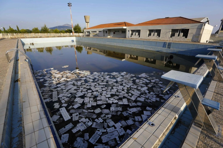 Image: Garbage floats in a deserted swimming pool at the Olympic Village in Thrakomakedones