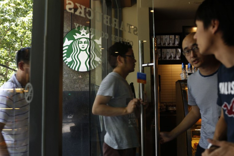 Image: Customers enter a Starbucks store in Shanghai