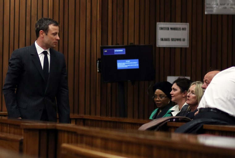 Oscar Pistorius looks at June Steenkamp (third left) and her husband Barry Steenkamp (right), as he walks past them at the high court in Pretoria on August 8, 2014.
