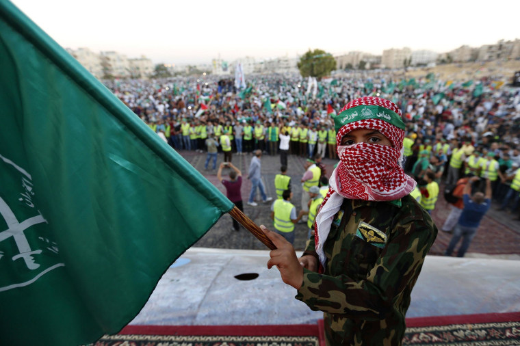 Image: A boy holds a Muslim Brotherhood flag during a rally in support of Palestinians in Gaza, in Amman