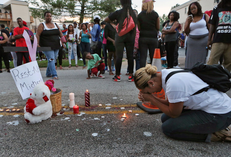 Meghan O'Donnell, 29, from St. Louis, prays on Sunday night at the spot where Michael Brown was killed earlier in the weekend.