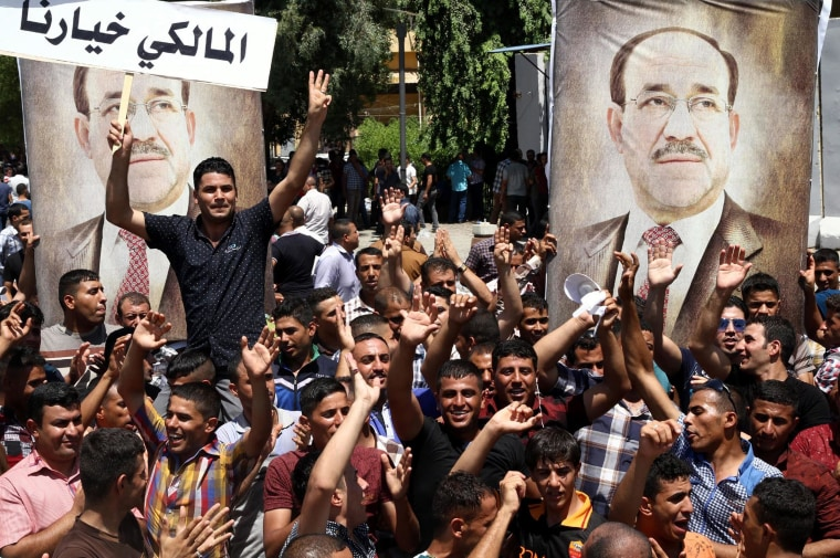 "Supporters of Iraqi Prime Minister Nouri al-Maliki carry his pictures and placards reading ""Maliki is our choice"" in Arabic in Baghdad on Monday."