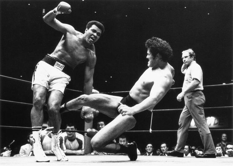 Japanese pro wrestler Antonio Inoki kicks the back of Muhammad Ali's leg