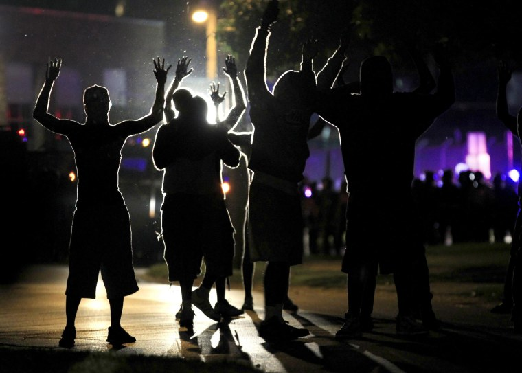 People raise their hands in the middle of the street as police wearing riot gear move toward their position trying to get them to disperse Monday, Aug. 11, 2014, in Ferguson, Mo.