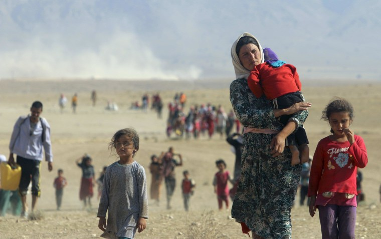 Image: Displaced people from the minority Yazidi sect walk toward the Syrian border