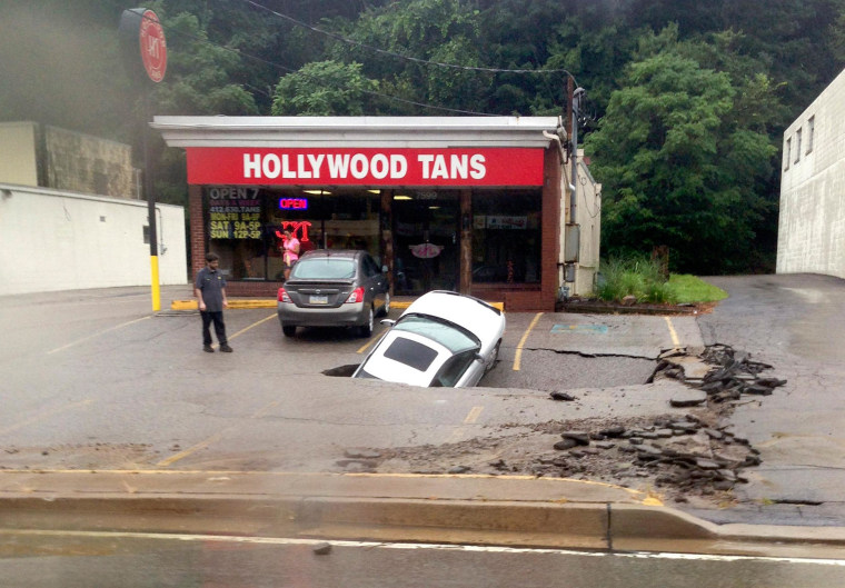 Image: A man looking at a car as it falls into a sinkhole on McKnight Road in Ross Township of Pittsburgh, Pennsylvania