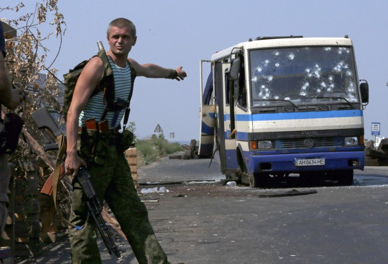 Image: An armed pro-Russian separatist points at a bus riddled with bullet holes at a checkpoint on the outskirts of Donetsk