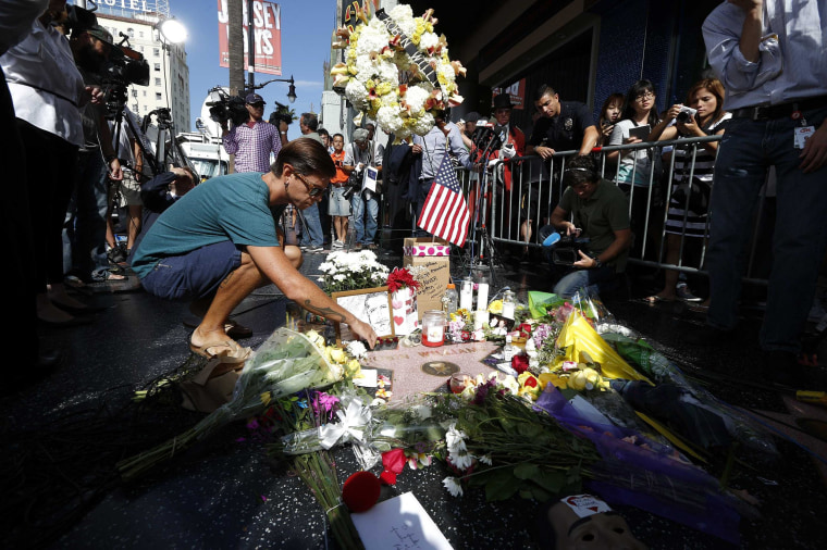 Brandon Scales lays flowers on the late Robin Williams' star on the Hollywood Walk of Fame in Los Angeles, Calif. on Aug. 12.