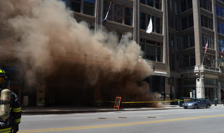 Image: Heavy smoke poured into the street after a series of small underground explosions in downtown Indianapolis