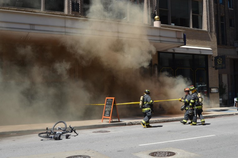 Image: Firefighters investigate a series of underground explosions in downtown Indianapolis