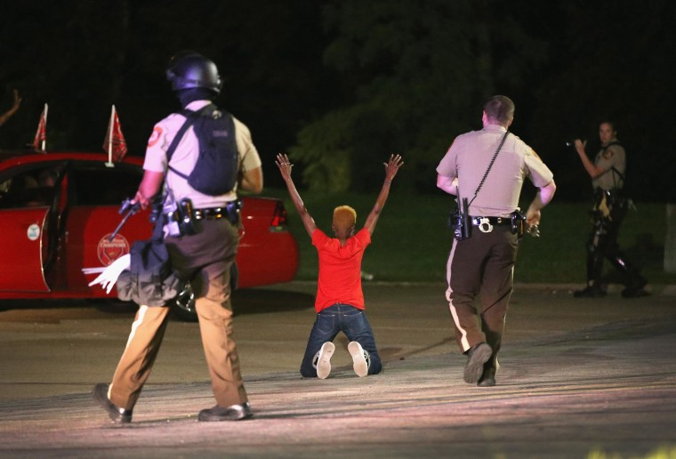 Police surround and detain two people in a car on Aug. 13, 2014 in Ferguson, Mo. Ferguson is experiencing its fourth day of unrest after following the shooting death of teenager Michael Brown on Saturday. Brown was shot and killed by a Ferguson police officer.