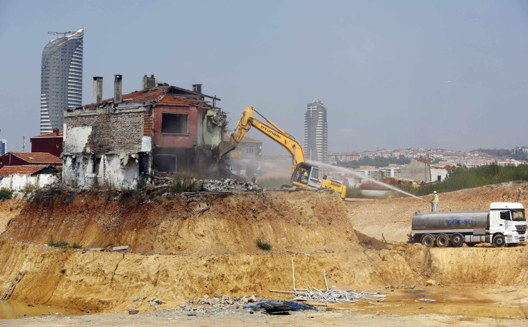 Image: An excavator demolishes a lone house at the construction site of an urban transformation project in Fikirtepe