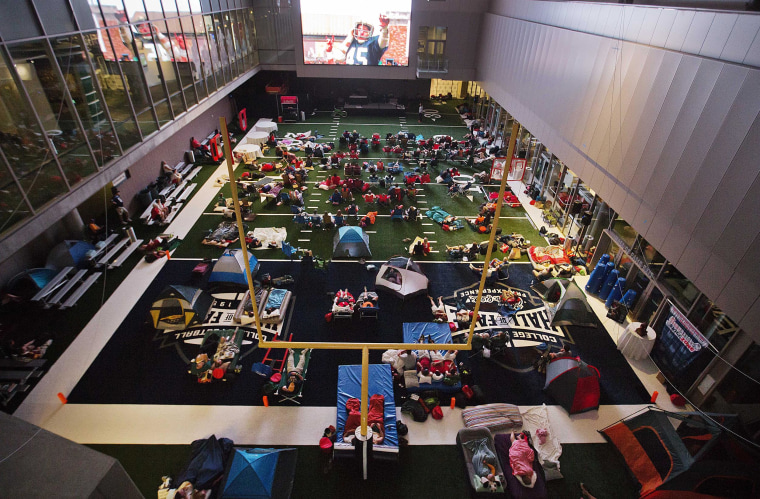 "Guests watch from the turf as the movie ""Rudy"" is plays during a sleepover in the College Football Hall of Fame in the early hours, on Aug. 14, in Atlanta. The crowd of 200 who came from as far away as Hawaii were among the first to experience the College Football Hall of Fame and Chick-fil-A Fan experience before it opened to the public on Aug. 23."