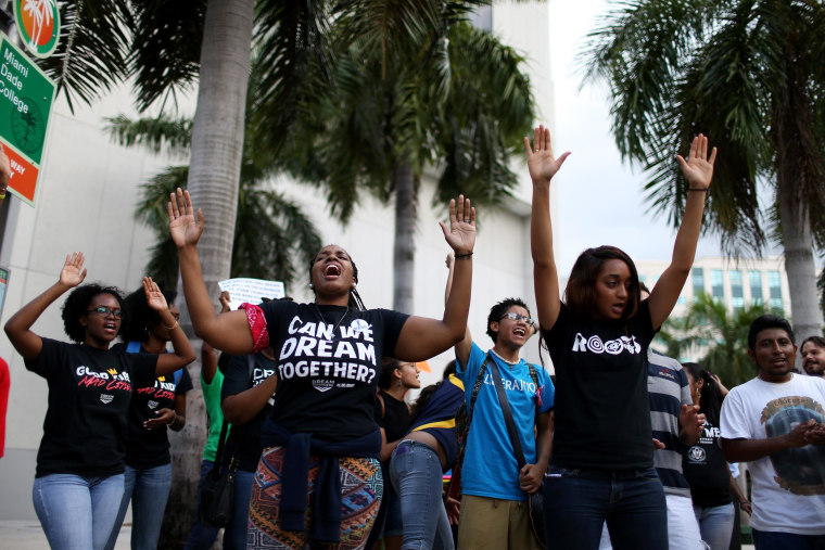 """Protesters raise their arms and shout """"hands up, don't shoot"""" outside the James Lawrence King Federal Justice Building where the U.S. Attorneys Office, Southern District of Florida, is located on August 14, 2014 in Miami, Florida. The protesters, which included members of the civil rights group Dream Defenders, say they want justice for Mike Brown, shot and killed by police in Ferguson, Missouri on August 9. They said they also want justice for 17-year old graffiti artist Israel Hernandez, who died from shock from a Miami Beach police officer's Taser last summer."""