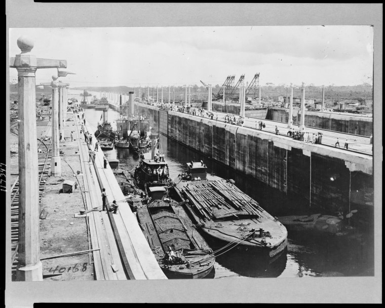 Image: Gatun locks looking toward Atlantic entrance of canal, showing tugs, dredges, and barges ready for first lockage from sea level up into Lake Gatun at the Panama Canal