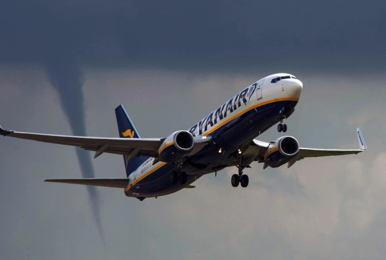 A funnel cloud is visible in the background as a Ryanair passenger plane takes off at East Midlands Airport