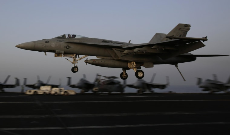 Image: An F/A-18C Hornet coming from Iraq lands on the flight deck of the U.S. Navy aircraft