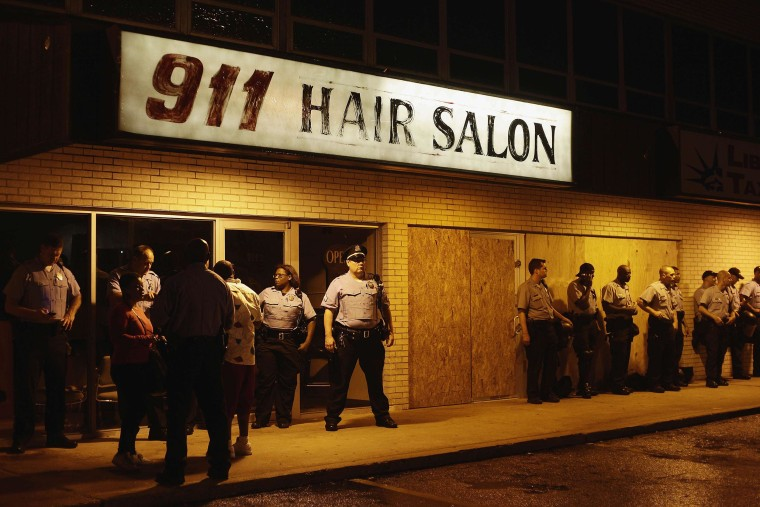 Police officers stand in position by the 911 Hair Salon as they watch demonstrators protest the shooting of Michael Brown on Aug. 16, in Ferguson, Mo.