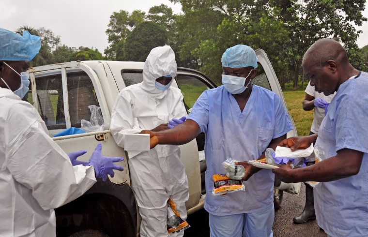 Health workers are handed personal protective gear by a team leader, right, before collecting the bodies of the deceased from streets in Monrovia, Liberia on Saturday.