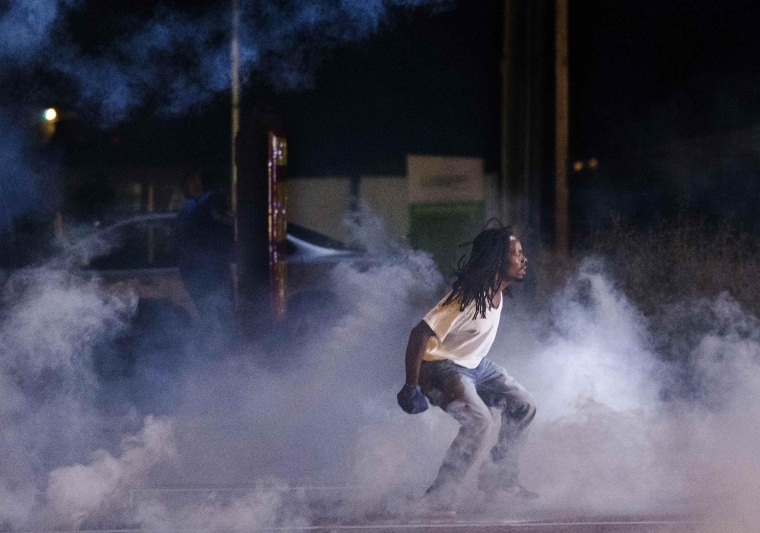 Image: A protester yells towards police in a cloud of tear gas after protests in reaction to the shooting of Michael Brown turned violent near Ferguson, Missouri