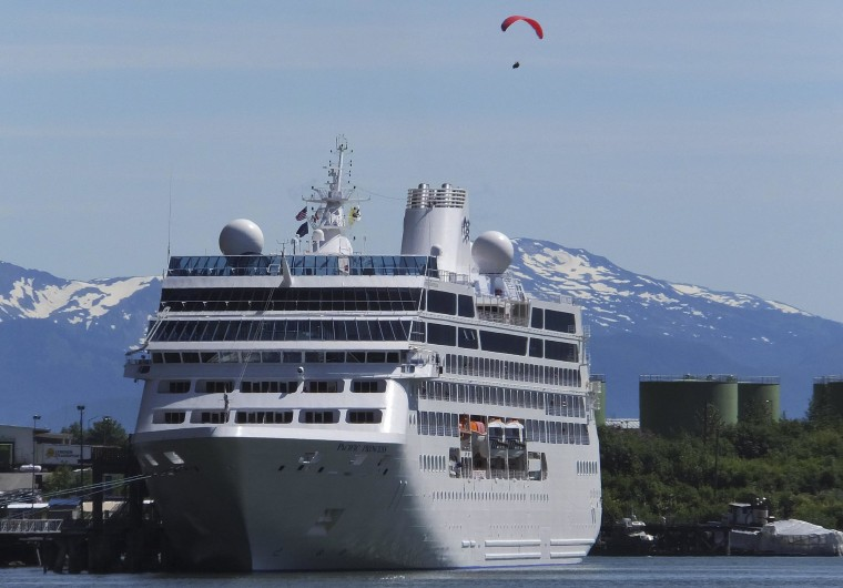 Image: A paraglider descends near a cruise ship docked in downtown Juneau, Alaska, on June 26, 2014.