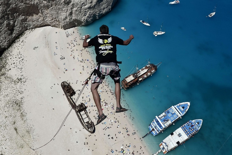 Lukas Michul, a member of the 'Dream Walker' group, jumps from atop the rugged rocks overlooking Navagio beach on the Greek island of Zakynthos, June 23, 2014.