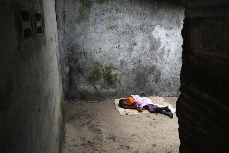 A very sick Saah Exco, 10, lies in a back alley of the West Point slum on Aug. 19 in Monrovia, Liberia. The boy was one of the patients that was pulled out of a holding center for suspected Ebola patients when the facility was overrun by a mob on Saturday.