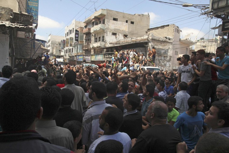 Palestinians watch as Hamas militants execute Palestinians suspected of collaborating with Israel in Gaza City on Aug. 22, 2014.